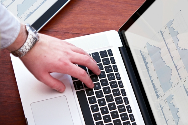 Person researching keywords for SEO on laptop computer
